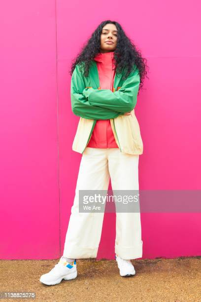 woman in bright colours with arms crossed - arme verschränkt stock-fotos und bilder