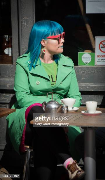 woman in bright green coat and blue hair outside cafe - gary colet stock pictures, royalty-free photos & images