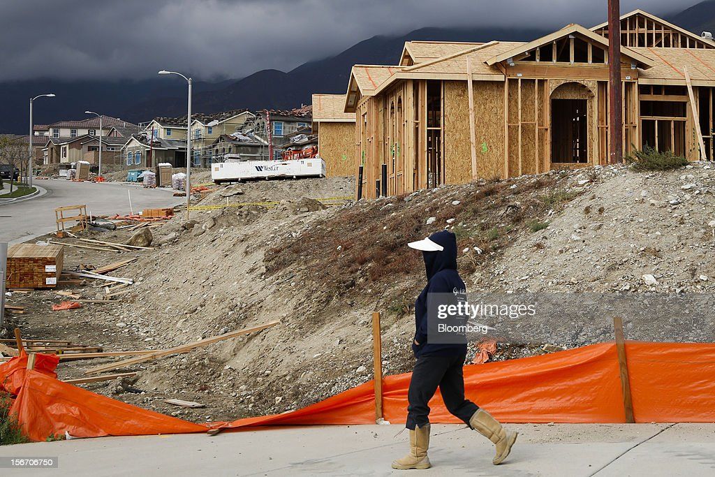A woman in brown boots and a white visor walks past houses under construction at the Ryland Homes Vista Heights development in Rancho Cucamonga, California, U.S., on Sunday, Nov. 18, 2012. The U.S. Census Bureau is scheduled to release housing starts figures on Nov. 20. Photographer: Patrick T. Fallon/Bloomberg via Getty Images