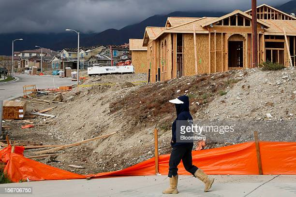 A woman in brown boots and a white visor walks past houses under construction at the Ryland Homes Vista Heights development in Rancho Cucamonga...