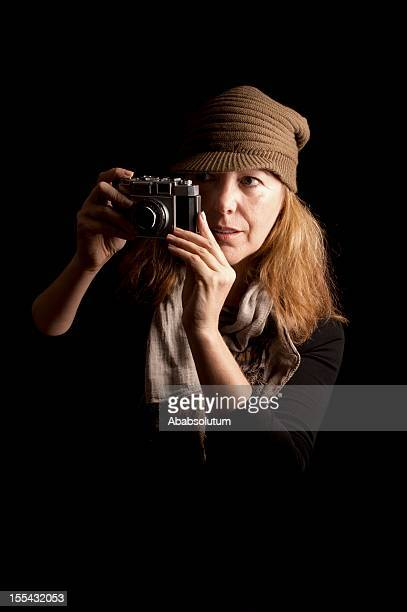 Woman in Brown Cap Photographing with Retro Camera