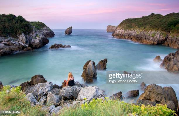 a woman in buelna beach at sunset, barro, asturias, llanes, spain. - llanes fotografías e imágenes de stock