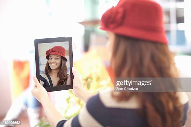 Woman in burgundy hat taking self portrait on digital tablet
