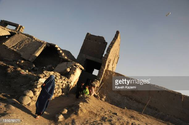 A woman in burka passes by children playing in the ruins of civil war under the watchful eye of a spy zeppelin on October 16 2011 in Kabul...