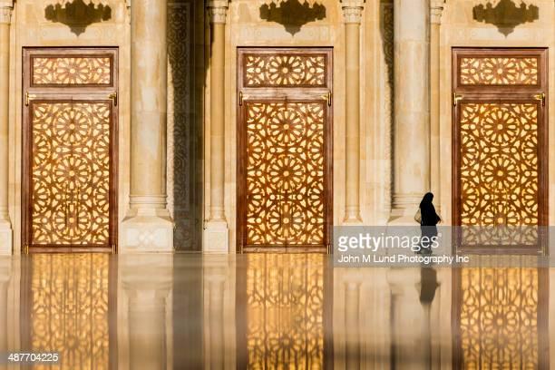 Woman in burka walking by ornate Saleh Mosque