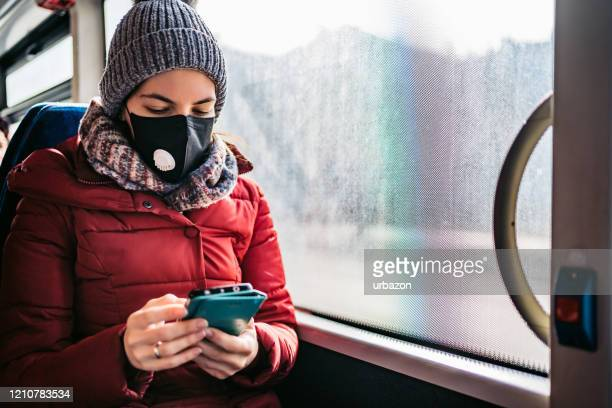 woman in bus wearing face mask - transporte público imagens e fotografias de stock