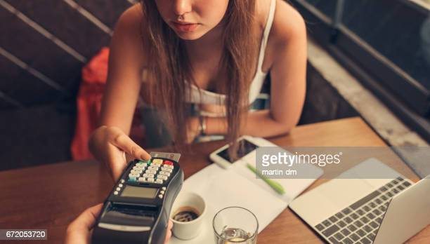 Woman in cafe paying with credit card