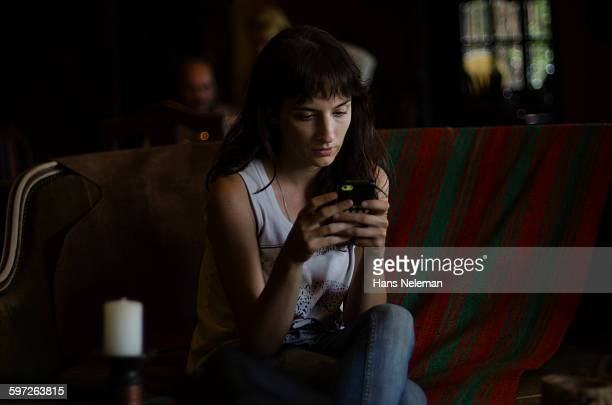Woman in cafe texting with mobile phone