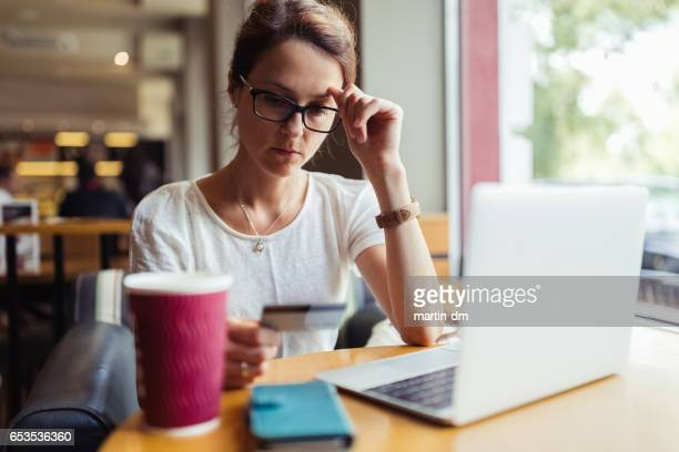 Woman in cafe using credit card for online payments