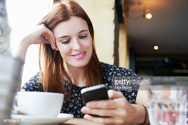 woman in cafe using mobile phone