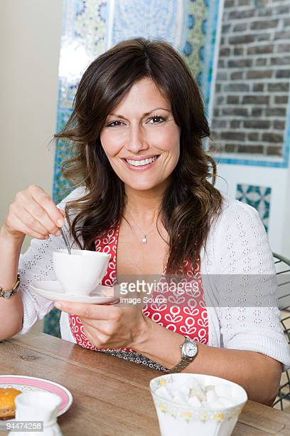 woman in cafe with cup of tea - saucer stock pictures, royalty-free photos & images
