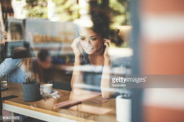 Woman in cafe with earphones and smart phone