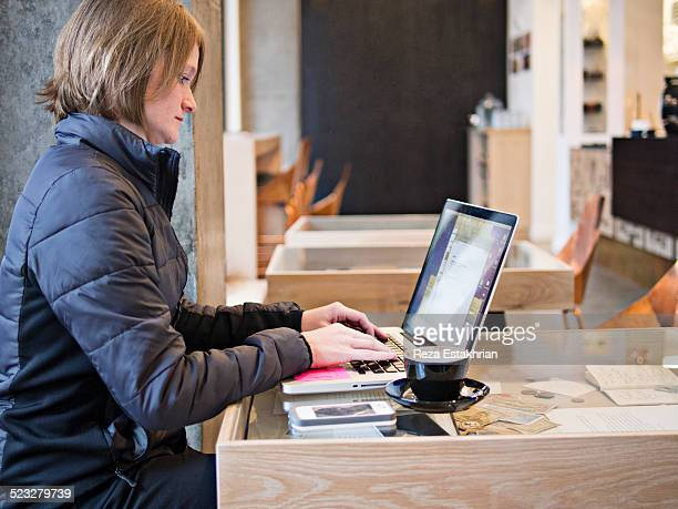 Woman in cafe works on laptop
