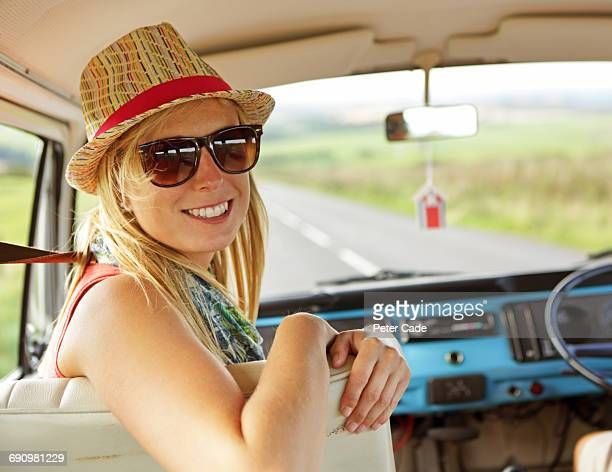 woman in camper van turnning and smiling behind - camper van stock pictures, royalty-free photos & images
