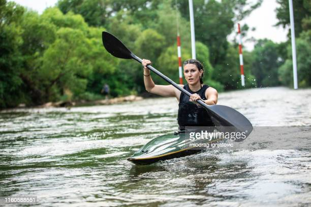 woman in canoe passing the gate - swift river stock photos and pictures