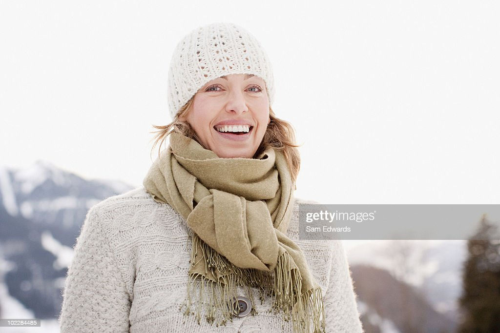 Woman in cap and scarf smiling : Stock Photo