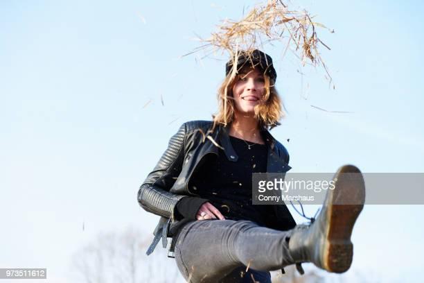 woman in cap kicking up straw against blue sky - bottes en cuir photos et images de collection
