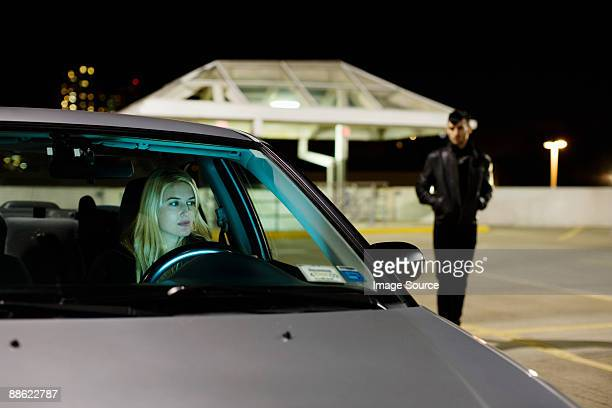 Woman in car and man in parking lot