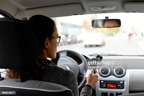Woman in car looking at smartphone