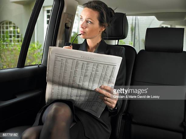Woman in car, reading newspaper