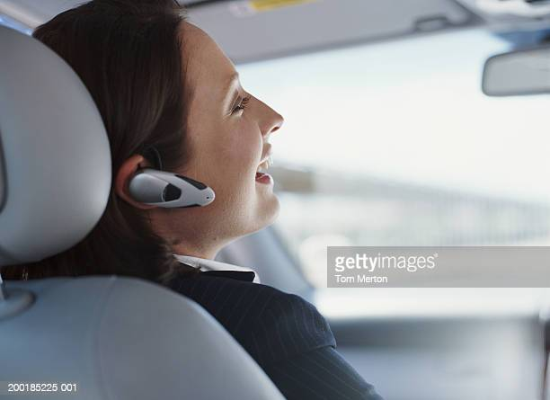 Woman in car using hands-free device, laughing, rear view