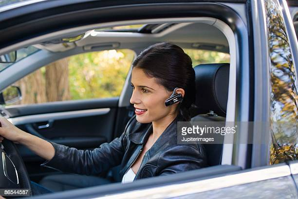 Woman in car with cell phone earphone