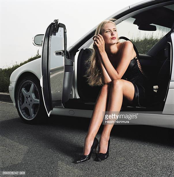Woman in car with door open looking away