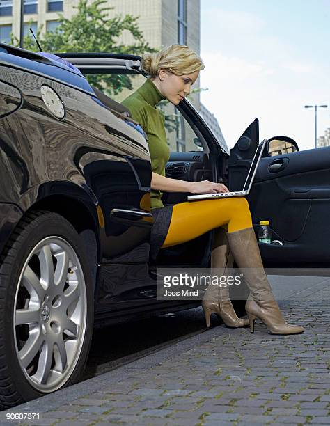 woman in car with door open, using laptop - short skirts in cars stock photos and pictures