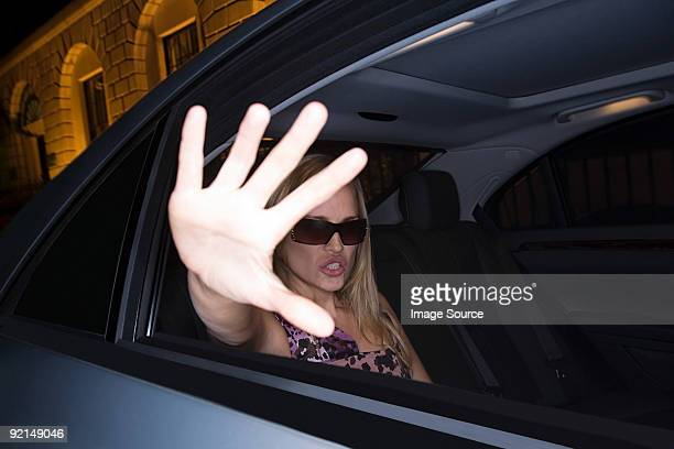 Woman in car with hand to camera