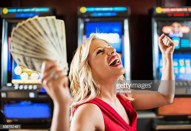 woman in casino winning at slot machine. - casino stock pictures, royalty-free photos & images