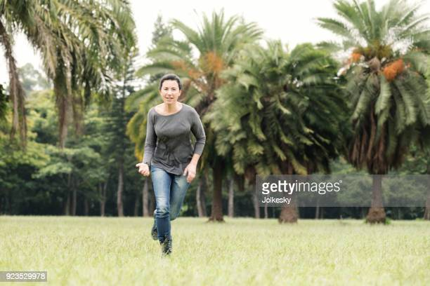 woman in casual clothing running in a grass area - retouched image stock photos and pictures