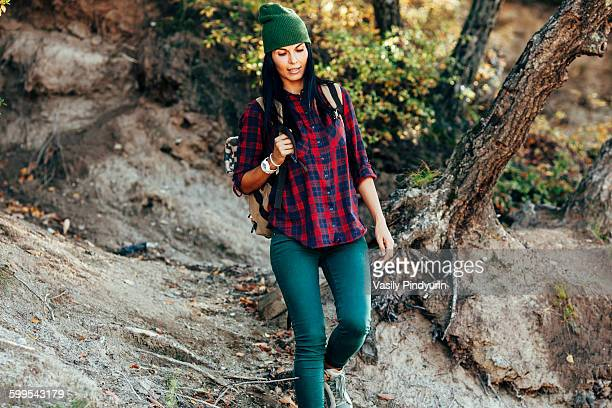 Woman in casuals hiking in forest
