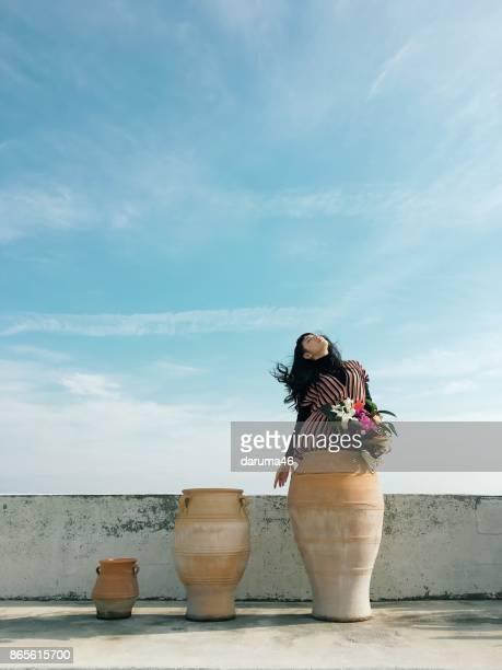 Frau in Keramikvase gegen Himmel