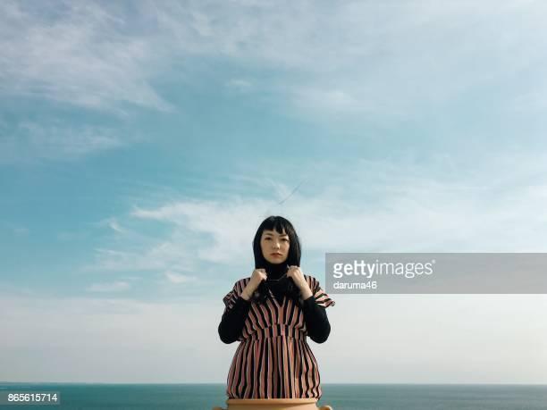 陶製の花瓶で空を背景に女性 - 決意 ストックフォトと画像
