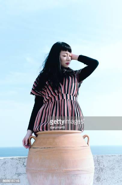 Woman in ceramic vase against sky