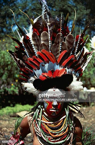 A woman in ceremonial dress wearing a feathered headdress Papua New Guinea