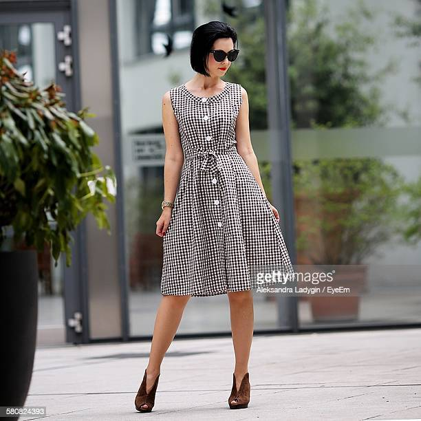 woman in checked pattern dress standing on street - checked dress stock pictures, royalty-free photos & images