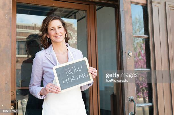 Woman in chef's apron in doorway holding Now Hiring sign