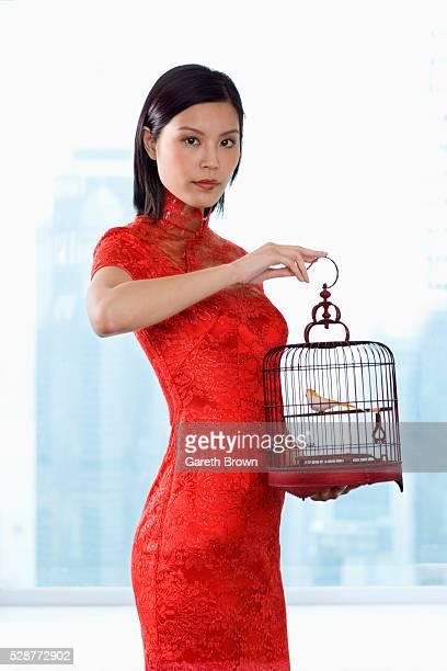 Woman in Cheongsam Holding Birdcage
