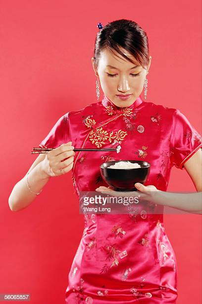 Woman in Cheongsam, holding bowl of rice and chopsticks, looking down