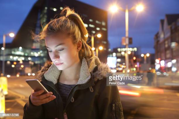 woman in city at night looking at phone - jacket stock pictures, royalty-free photos & images