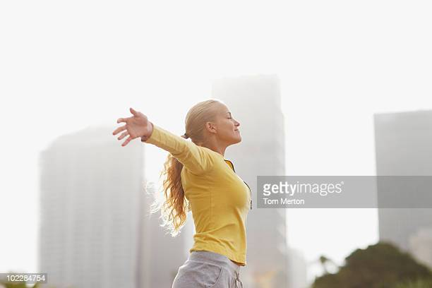 Woman in city with arms outstretched