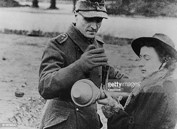 A woman in civilian clothes is trained in the use of a panzerfaust antitank rocket launcher Germany 1945