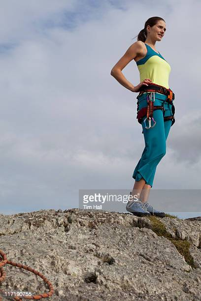 woman in climbing gear on top of rock