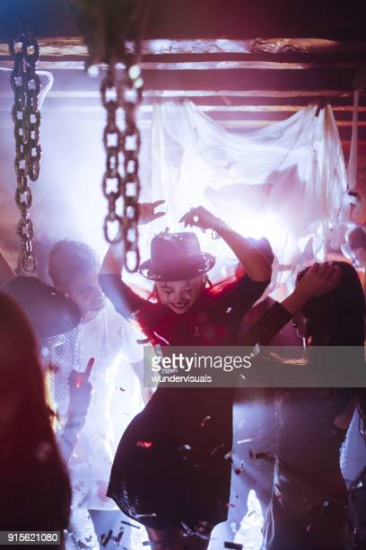 Woman in clown costume and make-up dancing at Halloween party