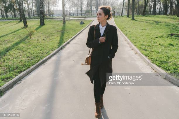 woman in coat and eyeglasses walking in the park - lunch break stock photos and pictures