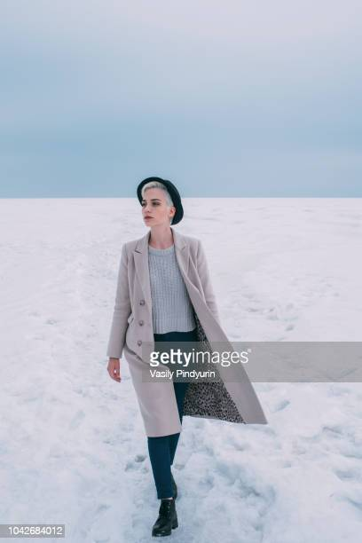woman in coat and hat walking in snow covered landscape - femme russe photos et images de collection