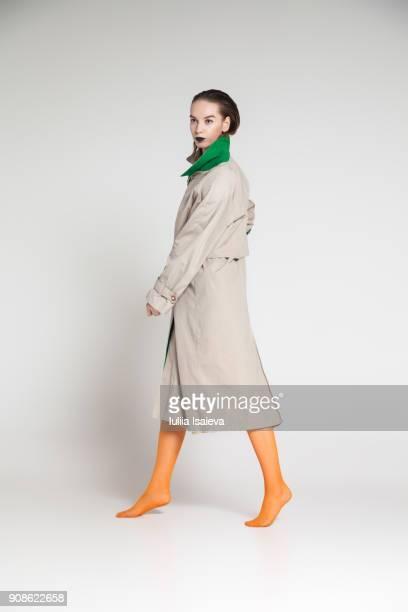 woman in coat stepping aside - トレンチコート ストックフォトと画像