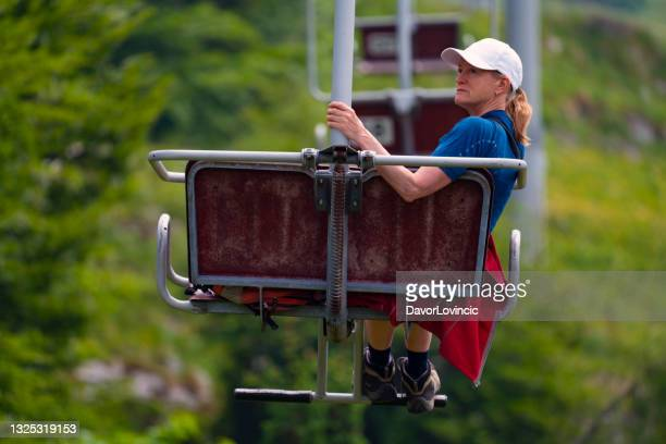 woman in coble chairlift seat with ski slope in background. - moment of silence stock pictures, royalty-free photos & images