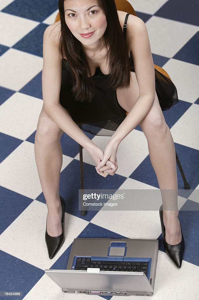 Woman in cocktail dress sitting in chair , laptop on the floor : Stockfoto